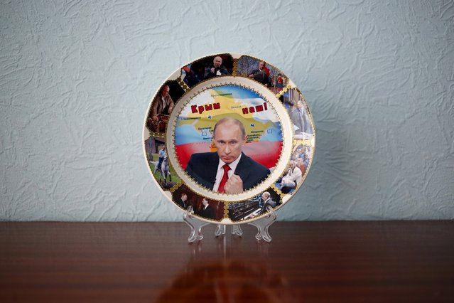 """A plate with a picture of Russian President Vladimir Putin and the phrase """"Crimea is ours"""" is seen in in this photo illustration taken in a hotel room in Kazan, Russia, July 24, 2015. (Photo by Stefan Wermuth/Reuters)"""