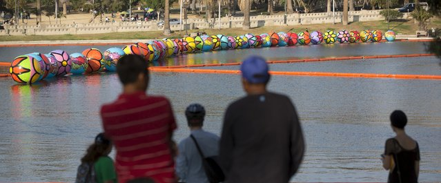 "People watch inflated spheres in MacArthur Park Lake during the installation of Portraits of Hope's exhibition ""Spheres at MacArthur Park"" in Los Angeles, California August 21, 2015. (Photo by Mario Anzuoni/Reuters)"