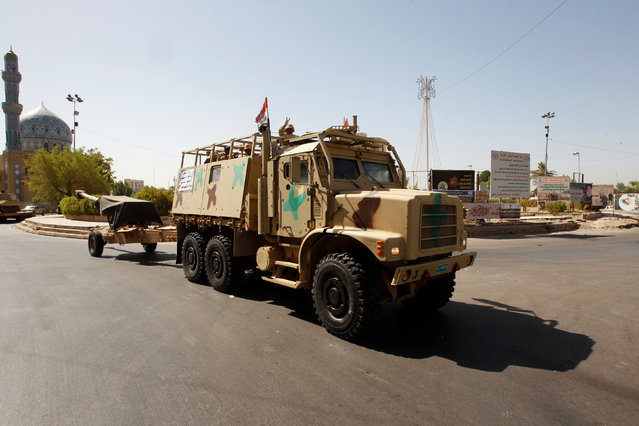 Iraqi security forces vehicles take part in a military parade in the streets of Baghdad, Iraq July 12, 2016. Social media activists posted images of tanks, armored vehicles, cannons, soldiers, police officers, and PMF members in Saadoun Street. The photos spiked a rumor of military coup. (Photo by Khalid al Mousily/Reuters)
