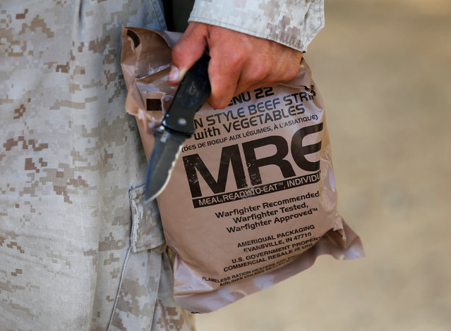 A U.S. Marine eats breakfast from an MRE ration during training as part of Rim of the Pacific (RIMPAC) 2016 exercise held at Camp Pendleton, California United States, July 13, 2016. (Photo by Mike Blake/Reuters)