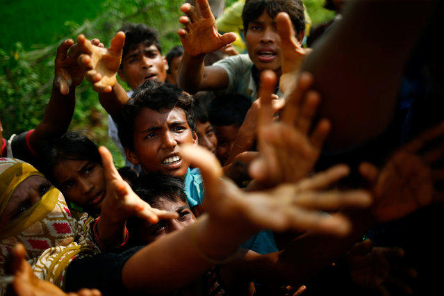 Rohingya refugees stretch their hands for food near Balukhali in Cox's Bazar, Bangladesh, September 4, 2017. (Photo by Mohammad Ponir Hossain/Reuters)