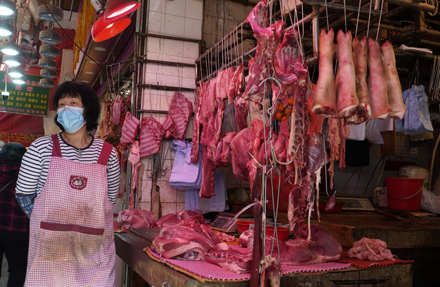 A vendor wears a face mask selling meat at a market in Hong Kong, Friday, January 31, 2020. The World Health Organization declared the outbreak sparked by a new virus in China that has spread to more than a dozen countries a global emergency after the number of cases spiked more than tenfold in a week, including the highest death toll in a 24-hour period reported Friday. (Photo by Vincent Yu/AP Photo)