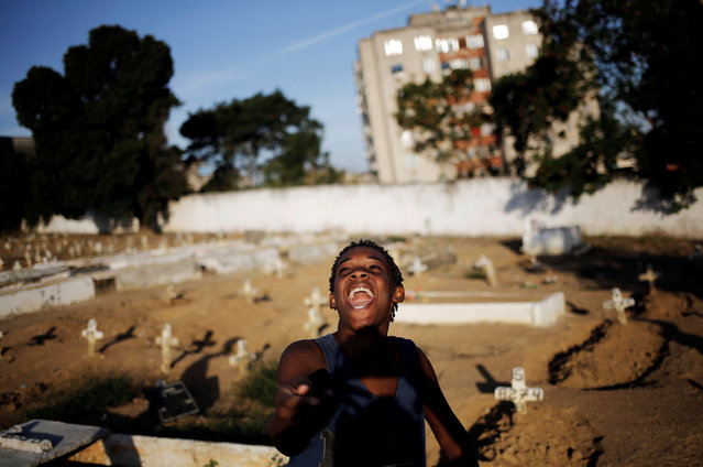 A boy flies his kite in a cemetery in the Vila Operaria Favela of Rio de Janeiro, Brazil, July 9, 2016. (Photo by Nacho Doce/Reuters)