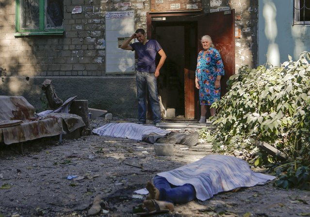 Local residents stand at a damaged apartment block near bodies of victims killed by what locals say was recent shelling by Ukrainian forces in Donetsk August 23, 2014. (Photo by Maxim Shemetov/Reuters)