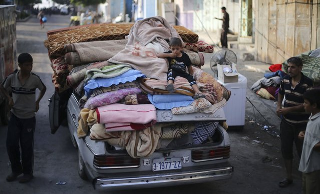 A Palestinian boy sits atop a car loaded with his family's belongings near their house, which witnesses said was hit by an Israeli air strike, in Rafah in the southern Gaza Strip August 26, 2014. (Photo by Ibraheem Abu Mustafa/Reuters)