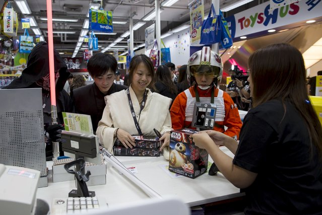 """Fans pay at the cashier to buy new toys from the upcoming film """"Star Wars: The Force Awakens"""" on """"Force Friday"""" in Hong Kong, China, September 4, 2015. (Photo by Tyrone Siu/Reuters)"""