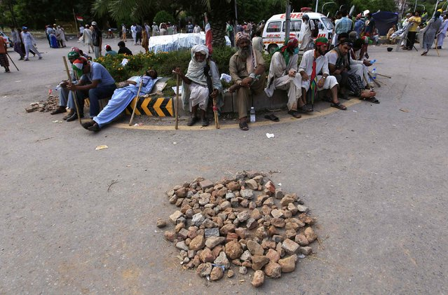 Anti-government protesters with sticks sit near stones at an intersection along a road during the Revolution March in Islamabad September 2, 2014. Pakistan's parliament threw its weight behind embattled Prime Minister Nawaz Sharif on Tuesday as a deepening crisis over violent protests demanding his resignation prompted fears of an army intervention. (Photo by Akhtar Soomro/Reuters)
