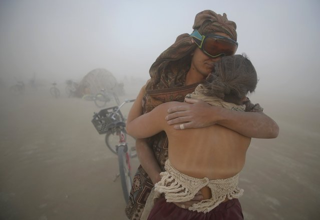 """Hank Allen and Sarah Duxbury embrace during a dust storm at the Burning Man 2015 """"Carnival of Mirrors"""" arts and music festival in the Black Rock Desert of Nevada, September 2, 2015. (Photo by Jim Urquhart/Reuters)"""
