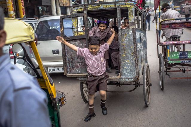A schoolboy jumps from a rickshaw on his way back from school on April 11, 2012 in New Delhi, India. (Photo by Daniel Berehulak/Getty Images)