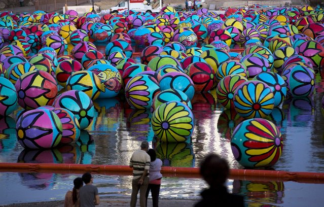 "People look at inflated spheres in MacArthur Park Lake, which are part of Portraits of Hope's exhibition ""Spheres at MacArthur Park"", in Los Angeles, California September 4, 2015. The installation will feature about 3,000 inflatable hand-painted spheres. (Photo by Mario Anzuoni/Reuters)"