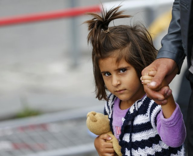 A migrant child walks after arriving by train to the main railway station in Munich, Germany September 6, 2015. Austria and Germany threw open their borders to thousands of exhausted migrants on Saturday, bussed to the Hungarian border by a right-wing government that had tried to stop them but was overwhelmed by the sheer numbers reaching Europe's frontiers. (Photo by Michael Dalder/Reuters)