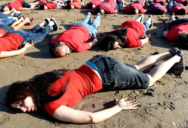 Moroccans adopt the position of the lifeless body of Syrian three-year-old Aylan Kurdi, who drowned while fleeing the Syrian war, during a rally to pay tribute to the tiny boy on September 7, 2015 on a beach in the capital Rabat. Aylan's body was photographed lying face down in the sand with red and blue clothing on a Turkish beach, in a bleak image that rapidly went viral on social media. (Photo by Fadel Senna/AFP Photo)