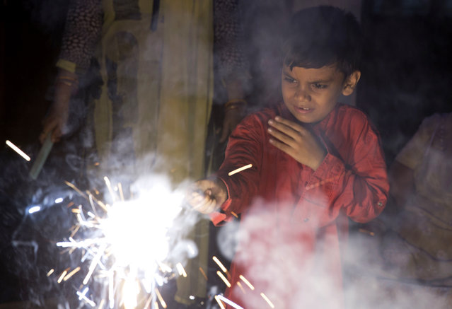 An Indian boy plays with firecrackers to celebrate Diwali, the Hindu festival of lights, in Allahabad, India, Thursday, October 19, 2017. (Photo by Rajesh Kumar Singh/AP Photo)