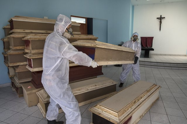 Funeral home workers prepare to load coffins into a waiting vehicle to transport to a public hospital in order to pick up bodies of deceased persons who are suspected to have died from the new coronavirus, at a crematorium in Lima, Peru on May 20, 2020. (Photo by Rodrigo Abd/AP Photo)