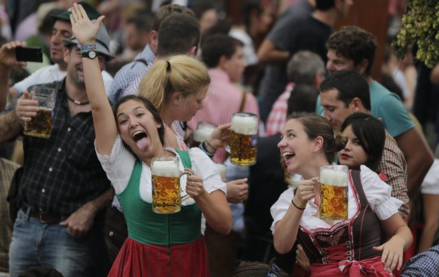 Young women celebrate the opening of the 181th Oktoberfest beer festival in Munich, southern Germany, Saturday, September 20, 2014. (Photo by Matthias Schrader/AP Photo)