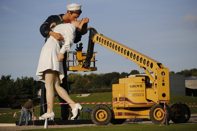 """Workers install the """"Unconditional Surrender"""" sculpture by artist Seward Johnson of the U.S. outside the Memorial of Caen museum in Caen, September 25, 2014. The 25-foot statue of a sailor kissing a nurse is to spend a year in front of the Caen Memorial, a museum known for its extensive collection documenting the Normandy invasion in 1944 and World War II. (Photo by Stephane Mahe/Reuters)"""