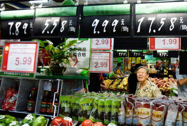 A woman looks at boards showing prices at a supermarket in Hangzhou, Zhejiang Province, China, August 9, 2016. (Photo by Reuters/China Daily)