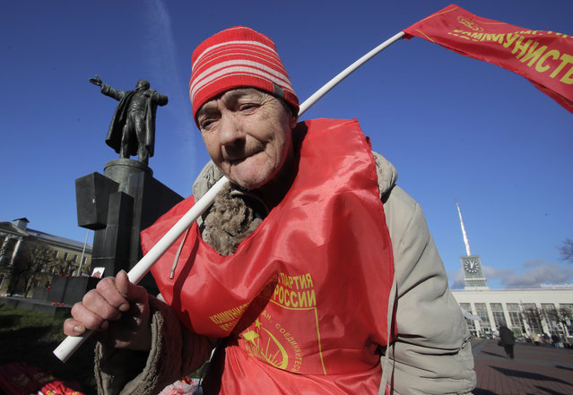 Communist Valentina, 73, attends celebration of the 100th anniversary of the 1917 Bolshevik revolution near a statue of Soviet Union founder Vladimir Lenin in St.Petersburg, Russia, Tuesday, November 7, 2017. (Photo by Dmitri Lovetsky/AP Photo)