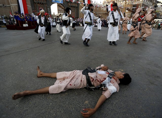 A Houthi follower with fake blood on his clothes lies on the ground to represent a victim as others perform a war dance during a ceremony marking the first anniversary of the Houthi movement's takeover of Yemen's capital Sanaa September 21, 2015. (Photo by Khaled Abdullah/Reuters)