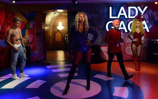 An employee walks near the wax statues of American singer Beyonce (C), Lady Gaga (R) and Canadian singer Justin Bieber (L) during the launch of Madame Tussauds Delhi museum in New Delhi on November 30, 2017. (Photo by Sajjad Hussain/AFP Photo)