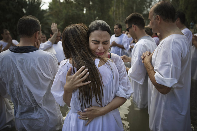 Christian pilgrims from Brazil embrace after they are baptized in the water of the Jordan River during a ceremony at the Yardenit baptismal site near the northern Israeli city of Tiberias October 15, 2014. (Photo by Finbarr O'Reilly/Reuters)