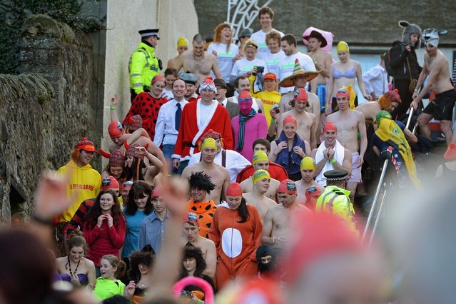SOUTH QUEENSFERRY, SCOTLAND - JANUARY 01: Revelers make their way down steps as they joined around 1,000 New Year swimmers, many in costume, braved freezing conditions in the River Forth in front of the Forth Rail Bridge during the annual Loony Dook Swim on January 1, 2013 in South Queensferry, Scotland. Thousands of people gathered last night to see in the New Year at Hogmanay celebrations in towns and cities across Scotland..  (Photo by Jeff J. Mitchell)