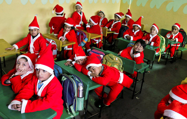 Children dressed in Santa Claus costumes sit inside a classroom before participating in Christmas celebrations at a school in Chandigarh, India, December 20, 2017. (Photo by Ajay Verma/Reuters)