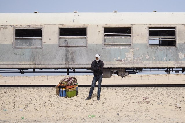 A passenger on a SNIM train carrying iron ore and mine workers waits for transport after arriving in Nouadhibou June 25, 2014. (Photo by Joe Penney/Reuters)