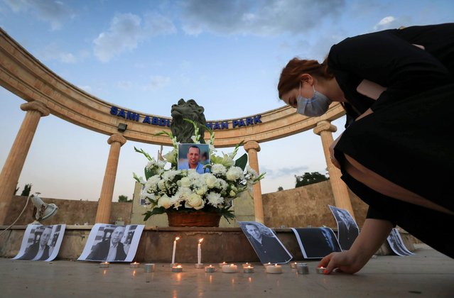 An Iraqi places a candle in front of a poster of slain Iraqi jihadism expert Hisham al-Hashemi, who was shot dead outside his house in the Iraqi capital, during a candlelight vigil in Arbil, the capital of the northern Iraqi Kurdish autonomous region, on July 11, 2020. The killing of the 47-year-old prominent expert has stirred fears Iraq is entering a dark and violent phase, as boiling tensions between pro-Iran factions and the government reach new heights. (Photo by Safin Hamed/AFP Photo)