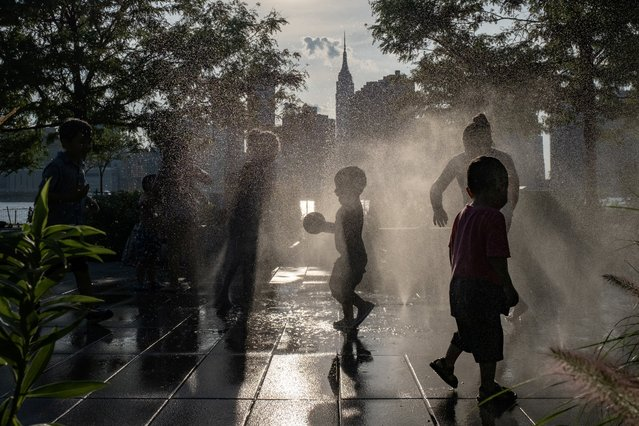 Children cool off in a fountain while enjoying a warm and humid day at Gantry Plaza State Park following the outbreak of the coronavirus disease (COVID-19), in Long Island City, New York, U.S., July 25, 2020. (Photo by Jeenah Moon/Reuters)