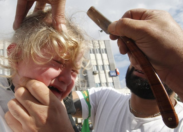 A Shi'ite Muslim girl reacts to a razor during a Muharram procession to mark Ashoura in Nabatieh town, southern Lebanon November 4, 2014. (Photo by Ali Hashisho/Reuters)