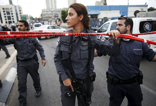 Israeli police officers patrol near a cordon at the scene of a stabbing attack in Tel Aviv, Israel October 8, 2015. Four people, including an Israeli soldier, were stabbed and wounded near a military headquarters in Tel Aviv on Thursday, police and ambulance sources said, as a rash of such Palestinian attacks spread to Israel's commercial capital. The assailant was shot and killed by another soldier as he fled, a police spokeswoman said. (Photo by Baz Ratner/Reuters)