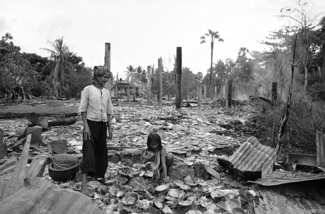 Cambodian woman and a little girl try to salvage belongings from what was once their home in Taing Kauk, about 47 miles North of Phnom Penh on October 9, 1970. Enemy forces occupied the village, then repulsed a Cambodian counter attack. The Cambodian forces used air and artillery strikes to drive the enemy out, resulting in flattening almost the entire village. The villagers had fled when the enemy arrived. (Photo by Ghislain Bellorget/AP Photo)