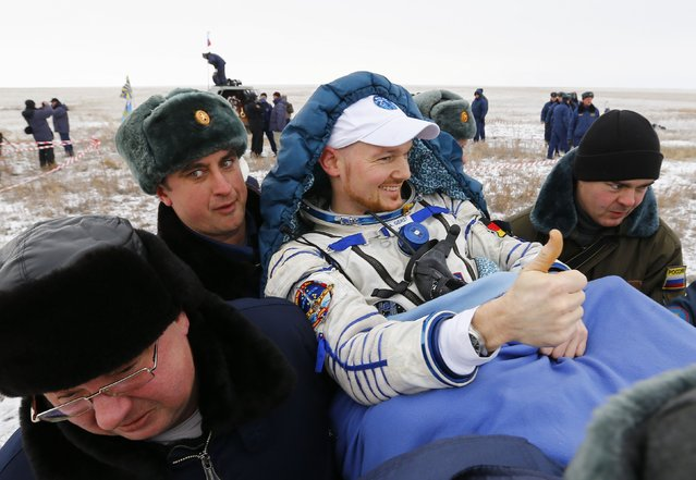 Ground personnel carry International Space Station (ISS) crew member Alexander Gerst of Germany shortly after landing near the town of Arkalyk in northern Kazakhstan November 10, 2014. (Photo by Shamil Zhumatov/Reuters)