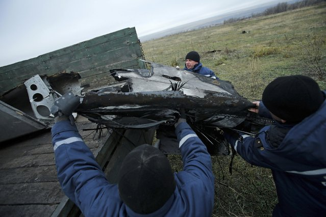 Local workers carry wreckage of the Malaysia Airlines Boeing 777 plane (flight MH17) at the site of the plane crash near the settlement of Grabovo in the Donetsk region November 16, 2014. (Photo by Antonio Bronic/Reuters)
