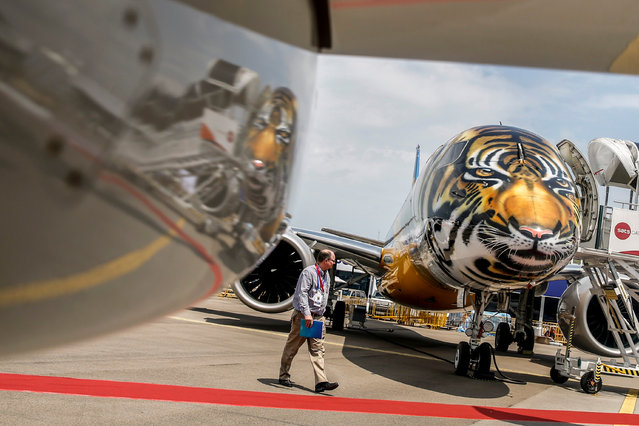 A man looks at an Embraer E190-E2 commercial jet with a tiger design painted on its nose while it is reflected in a nacelle of another aircraft at the static display ahead of the Singapore Airshow at the Changi Exhibition Centre in Singapore, 04 February 2018. The Singapore Airshow will take place from 06 to 11 February 2018 and will showcase aviation and defense technologies from around the world. (Photo by Wallace Woon/EPA/EFE)