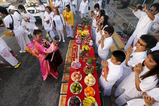 A devotee of the Chinese Ban Tha Rue shrine prays with people in front of an altar celebrating the annual vegetarian festival in Phuket, Thailand, October 17, 2015. (Photo by Jorge Silva/Reuters)