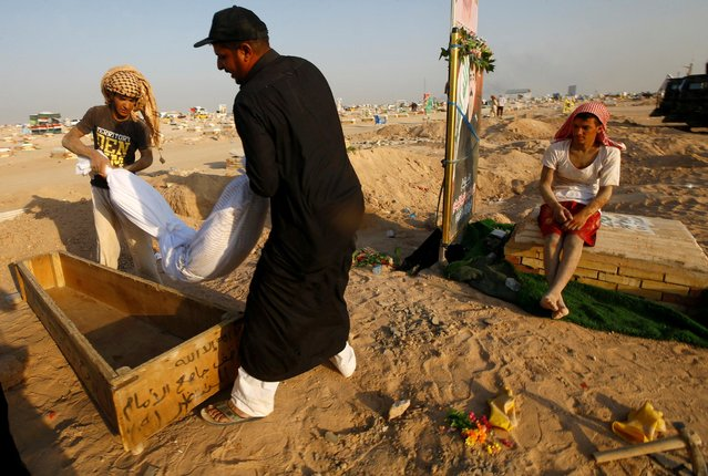 """Iraqi men carry the corpse of a man who, according to his relatives, died of the coronavirus, after they dug it up to be transferred to the """"Valley of Peace"""" cemetery on the outskirts of the holy city of Najaf, Iraq on September 12, 2020. (Photo by Alaa Al-Marjani/Reuters)"""