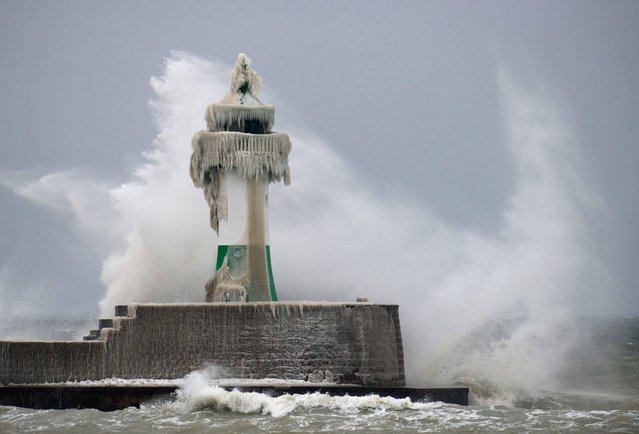 A wave hits an ice covered lighthouse in Sassnitz on the island of Ruegen in the Baltic Sesa, northern Germany, Tuesday, March 19, 2013. Unfriendly winter weather continues in northern and eastern Germany on the last day of winter. (Photo by Stefan Sauer/AP Photo/Dpa)