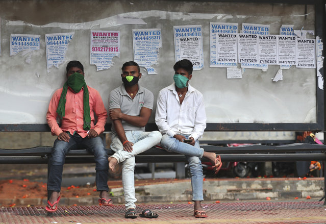 Indians wearing face masks as a precaution against the coronavirus wait at a bus stop in Bengaluru, India, Sunday, October 11, 2020. (Photo by Aijaz Rahi/AP Photo)