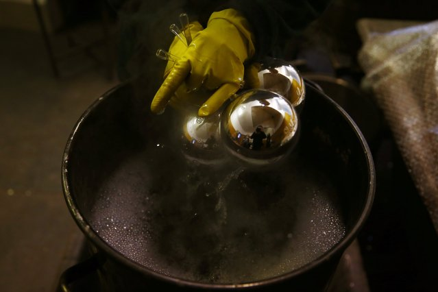 Glass baubles are coated with a chemical process at the Silverado manufacture of hand-blown Christmas ornaments in the town of Jozefow outside Warsaw December 2, 2014. (Photo by Kacper Pempel/Reuters)
