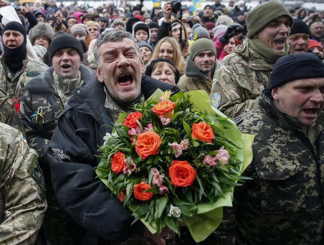 "Servicemen of ""Kiev 12"" military defence battalion react as they take part in a welcoming ceremony in central Ukrainian capital Kiev December 6, 2014. (Photo by Gleb Garanich/Reuters)"