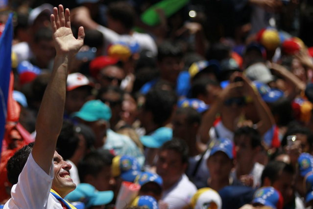 Venezuela's opposition leader and presidential candidate Henrique Capriles greets supporters during a campaign rally in the state of Guarico April 8, 2013. Venezuela will hold presidential elections on April 14. (Photo by Carlos Garcia Rawlins/Reuters)