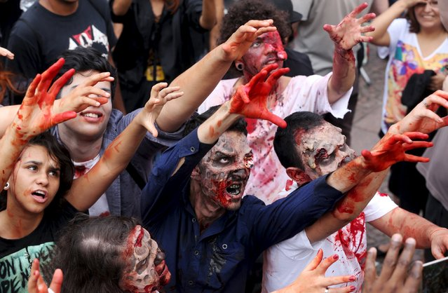 "Revellers with their bodies and faces painted attend the ""Zombie Walk"" parade in Sao Paulo, Brazil, November 2, 2015. (Photo by Paulo Whitaker/Reuters)"