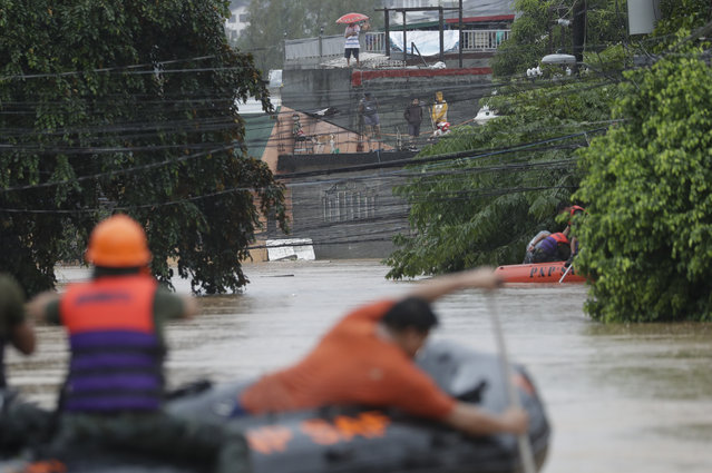 Trapped residents look from their roofs as rescuers go to their area in Marikina, Philippines due to Typhoon Vamco on Thursday, November 12, 2020. (Photo by Aaron Favila/AP Photo)