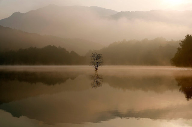 A view of morning mist lifting from a lake are seen in Yi county, in eastern China's Anhui province on October 30, 2020. (Photo by AFP Photo/Stringer)
