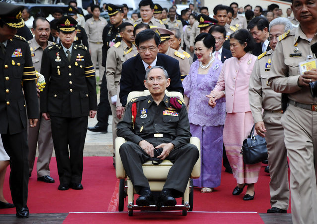 In this May 25, 2012, file photo, Thailand's King Bhumibol Adulyadej, center, is pushed in a wheelchair as he arrives at a rice field in Ayutthaya province, central Thailand. Thailand's Queen Sirikit, in purple, is walking at rear with Princess Sirindhorn. (Photo by AP Photo)