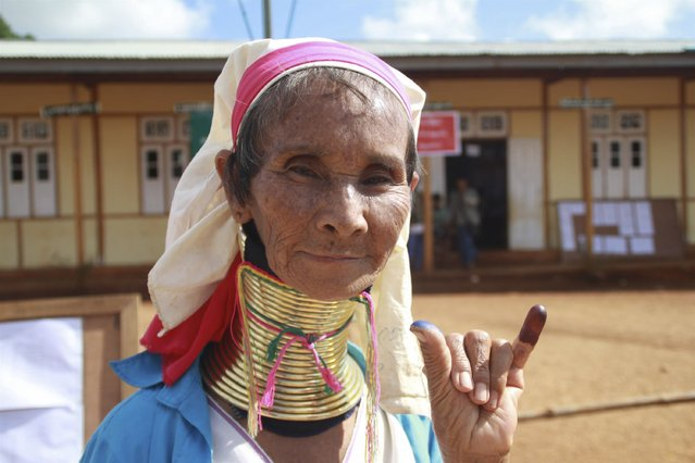 A Kayan woman, from one of Myanamr's ethnic minority groups, shows her ink-stained finger after she voted, in front of a polling station in Panpet village, Demoso township, Kayah state November 8, 2015. (Photo by Nay Lynn Thike/Reuters)