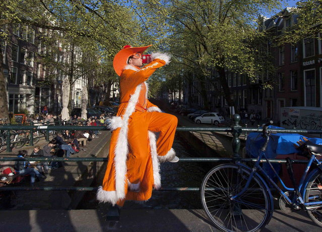 A man dressed in orange poses as he drinks on the Prinsengracht in Amsterdam April 29, 2013. The Netherlands is preparing for Queen's Day on April 30, which will also mark the abdication of Queen Beatrix and the investiture of her eldest son Willem-Alexander. (Photo by Cris Toala Olivares/Reuters)