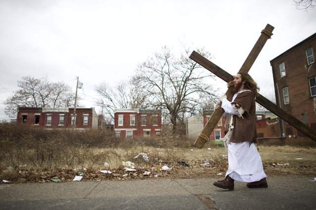 "Michael Grant, 28, ""Philly Jesus"", carries a 12 foot cross 8 miles through this blighted area of North Philadelphia towards LOVE Park in Center City as part of a Christmas walk to spread the true message of the holiday in Philadelphia, Pennsylvania December 20, 2014. As many as a half dozen others joined him for numerous miles as he trekked southward down Broad Street.  Some shouted ""Praise Jesus!"" and ""Thank you for doing this!"" at the sight. (Photo by Mark Makela/Reuters)"